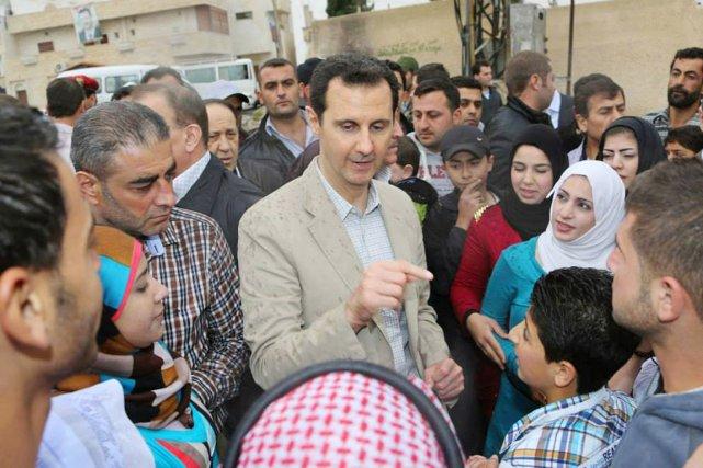 Le président Bachar al-Assad s'entretient avec des citoyens... (PHOTO AP/SANA)