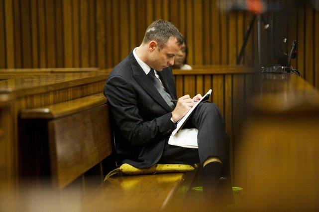 Oscar Pistorius prend des notes durant son procès... (PHOTO ALET PRETORIUS, ARCHIVES AFP)