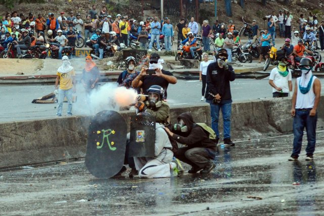 Des manifestants anti-Maduro se heurtent aux policiers, à... (PHOTO CARLOS BECERRA, AFP)