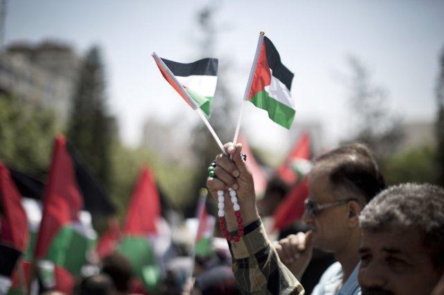 Un homme brandit deux petits drapeaux palestiniens, lors... (PHOTO MAHMUD HAMS, ARCHIVES AFP)