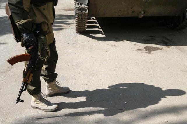 Un séparatiste pro-russe en treillis militaires monte la... (Photo: Reuters)