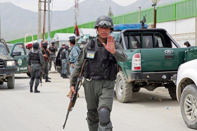 Un policer afghan empêche des journalistes d'approcher de... (PHOTO MASSOUD HOSSAINI, AP)