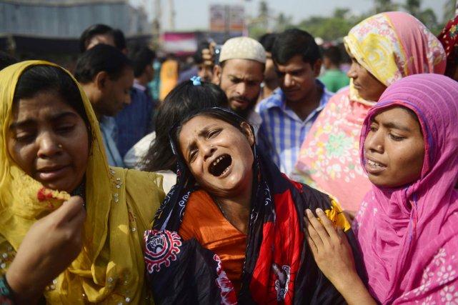 Des proches des salariés tués et des blessés,... (PHOTO MUNIR UZ ZAMAN, AFP)