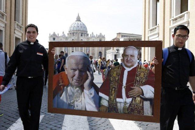 Deux prêtres transportent des photos des papesJean-Paul II... (PHOTO STEFANO RELLANDINI, REUTERS)
