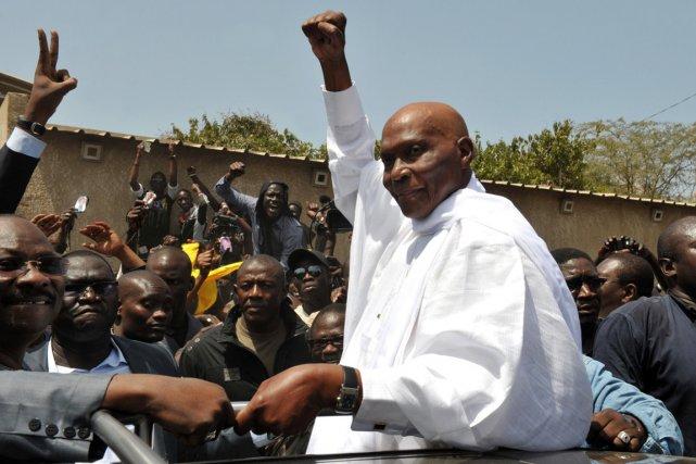 Le président sortant Abdoulaye Wade lève le poing... (PHOTO ARCHIVES AFP/SEYLLOU)