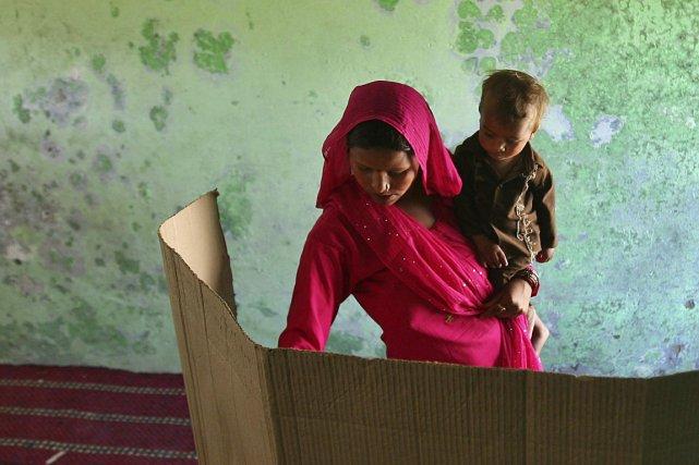 Une femme tenant son enfant dans un bureau... (Photo Reuters)