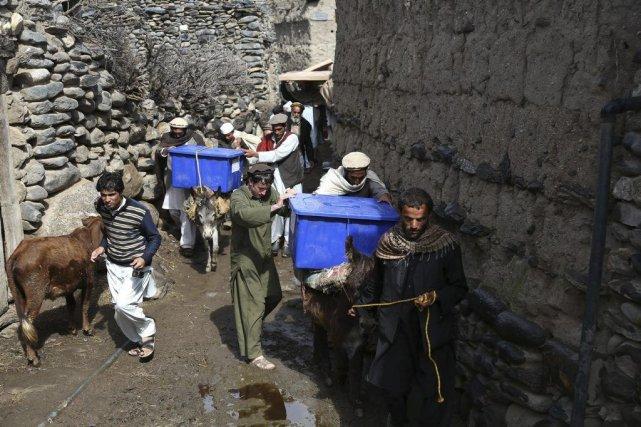 Des employés transportent du matériel électoral pour la... (Photo Rahmat Gul, archives AP)