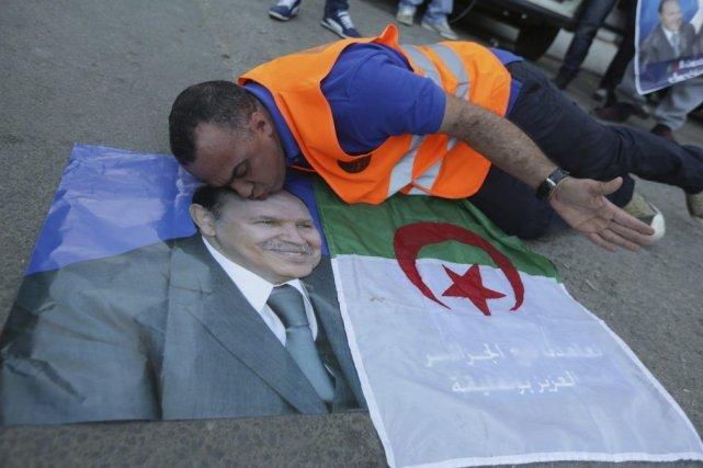 Un partisan du présidentBouteflika embrasse sa photo, le... (PHOTO PATRICK BAZ, AFP)