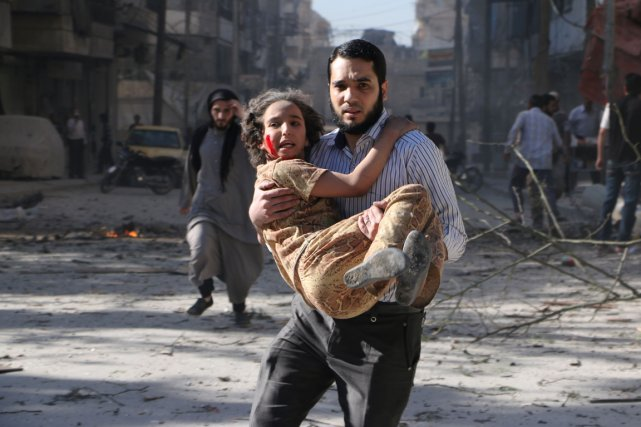 Un homme transporte une jeune fille blessée lors... (PHOTO AFP / AMC)