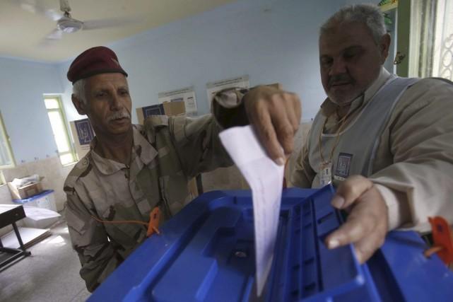 Un soldat irakien dépose son bulletin de vote... (Photo Mohammed Sawaf, Agence France-Presse)