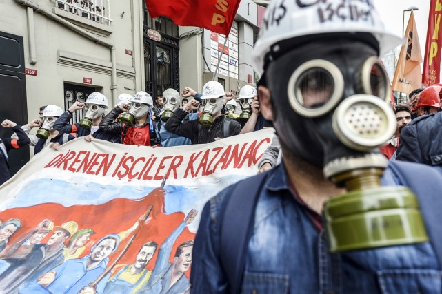 Des manifestants munis de masque à gaz défilent... (PHOTO GURCAN OZTURK, AFP)