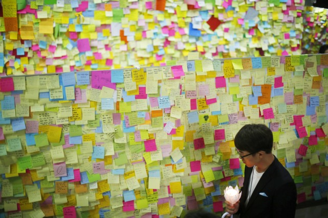 Un proche d'une victime regarde des messages écrits... (PHOTO KIM HONG-JI, ARCHIVES REUTERS)