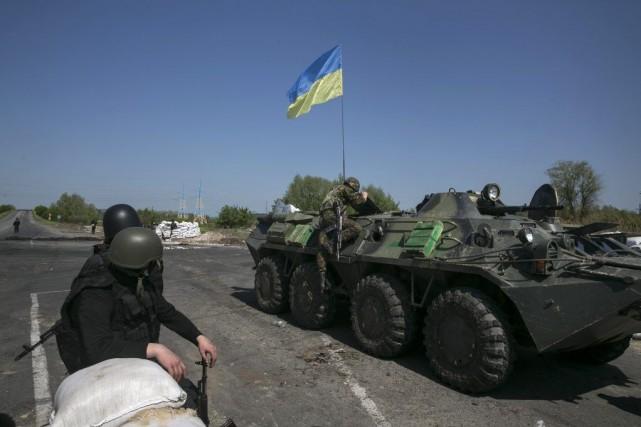 Un soldat ukrainien grimpe sur un char d'assaut... (PHOTO BAZ RATNER, REUTERS)