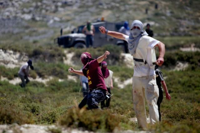 Des colons juifs lancent des pierres en direction... (PHOTO ARCHIVES AP)