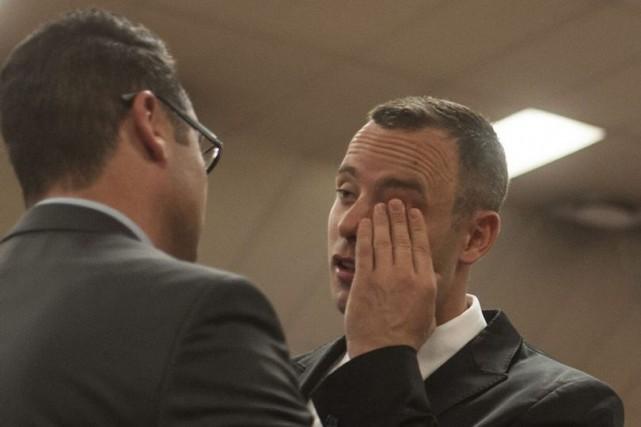 Oscar Pistorius (à droite) est consolé par son... (PHOTO IHSAAN HAFFEJEE, AP)