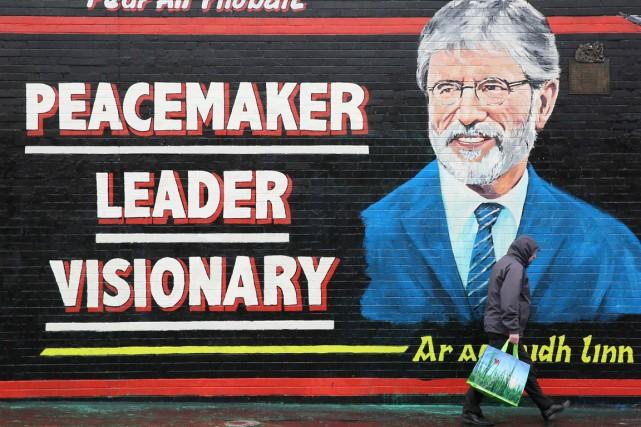 Un homme passe devant un graffiti à l'effigie... (PHOTO PAUL HACKETT, REUTERS)
