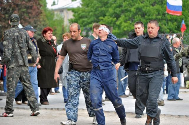 Des miliciens pro-russes ont escorté un homme aux... (Photo: AFP)