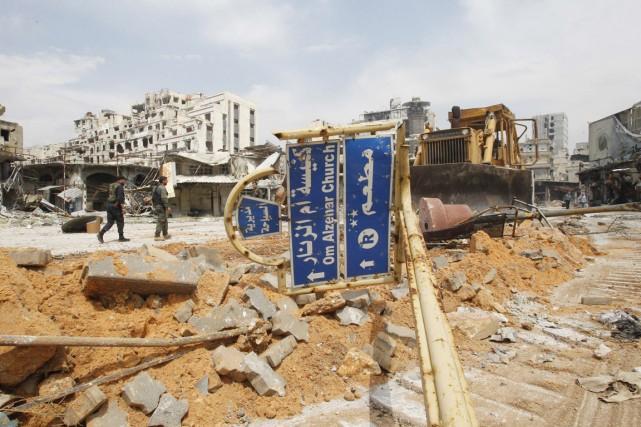 Des soldats syriens marchent dans le quartier dévasté... (PHOTO KHALED AL-HARIRI, REUTERS)