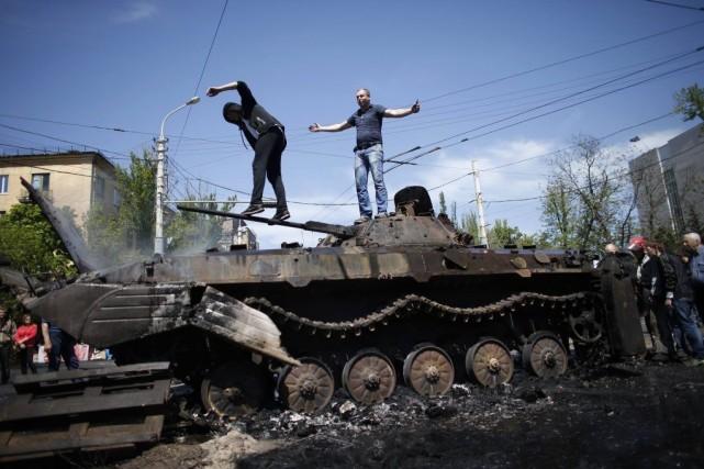 Deux hommes sont montés sur un char d'assaut... (PHOTO MARKO DJURICA, REUTERS)