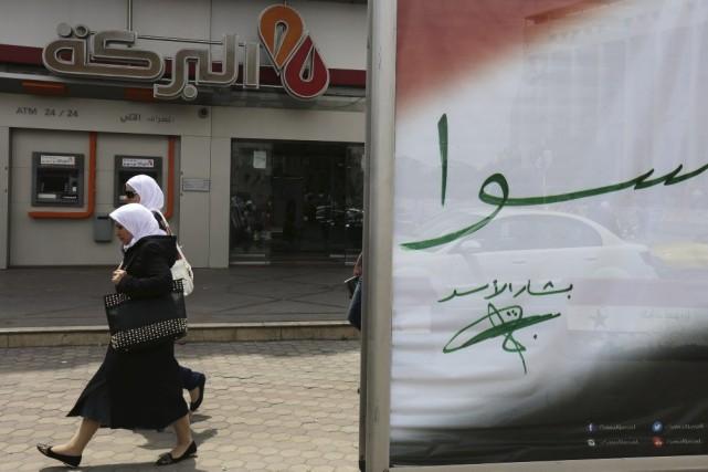 Deux femmes passent devant unpanneau d'affichage électoral du... (PHOTO LOUAI BESHARA, AFP)