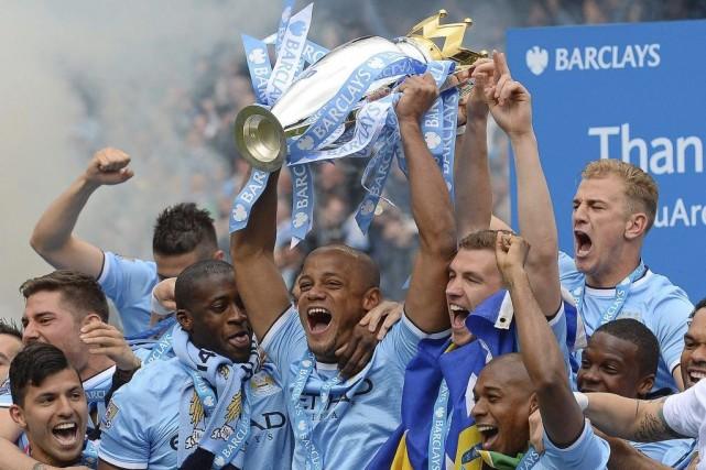 Vincent Kompany (au centre) soulève le trophée, entouré... (PHOTO ANDREW YATES, AFP)