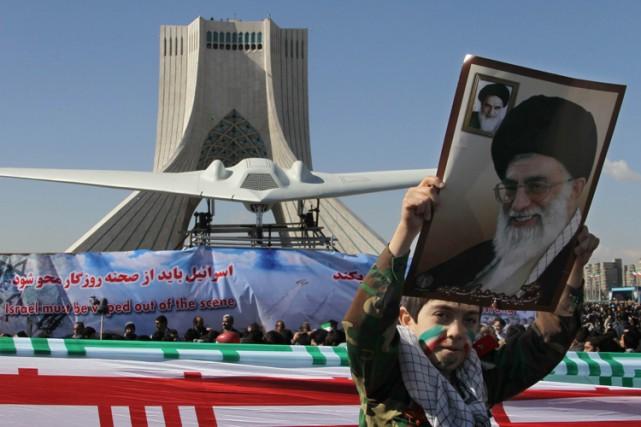 Un garçon iranien brandit le portrait de l'ayatollah... (Photo: AFP)