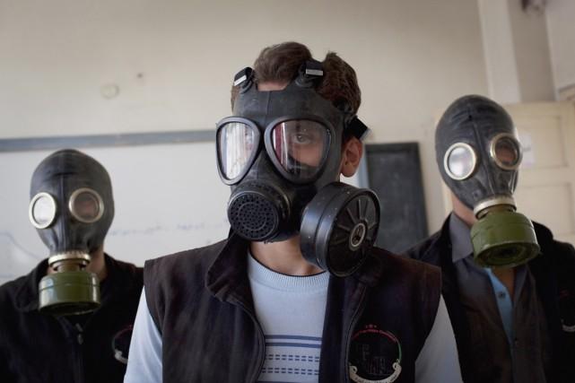 Des bénévoles portent le masque à gaz alors... (PHOTO JM LOPEZ, ARCHIVES AFP)