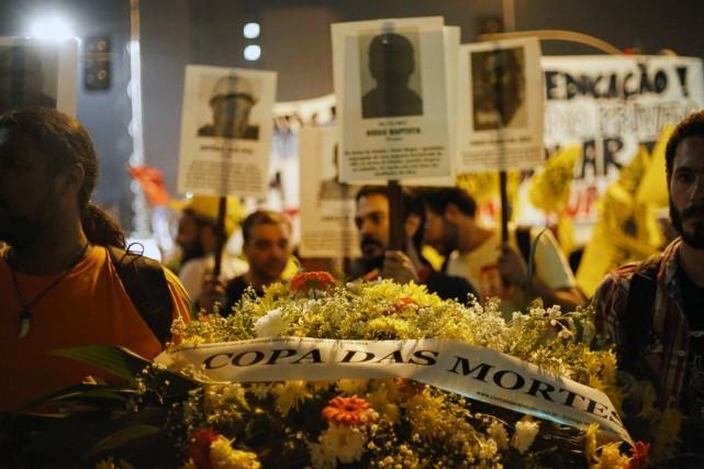Des manifestants portent une gerbe de fleurs sur... (Photo Miguel Schincariol, AFP)