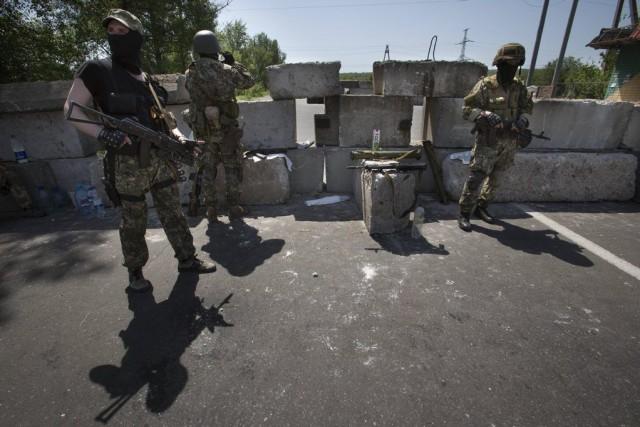 Des militants prorusses surveillent un barrage sur l'autoroute... (Photo Alexander Zemlianichenko, AP)