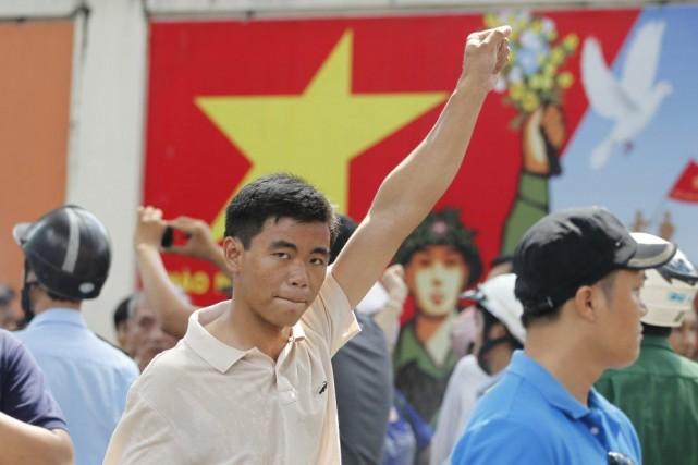 Un protestataire brandit le poing pendant une manifestation... (PHOTO PETER NG, REUTERS)