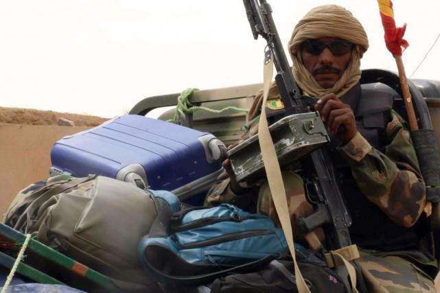 Un militaire malien est assis à l'arrière d'une... (PHOTO FABIEN OFFNER, AFP)