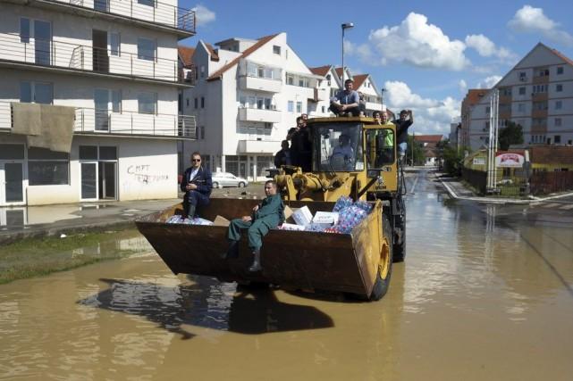 Des secouristes serbes distribuent des provisions dans les... (PHOTO ALEXA STANKOVIC, AFP)