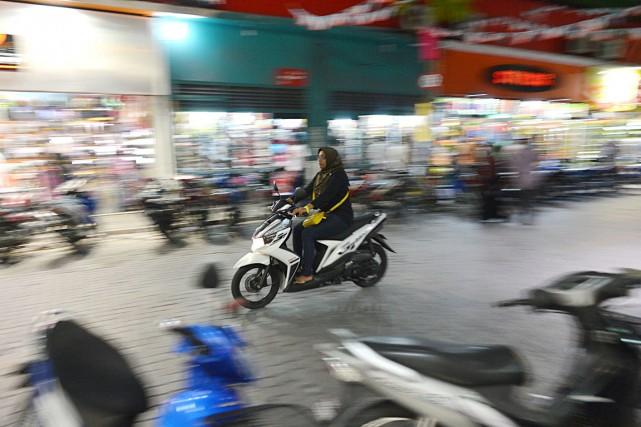 Une femme circule en scooter dans une rue... (PHOTO ISHARA S. KODIKARA, ARCHIVES AFP)