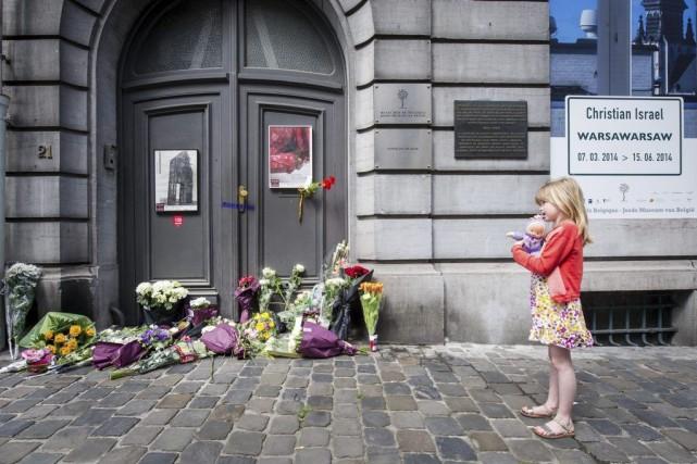 Une jeune fille regarde les fleurs déposées devant... (PHOTO GEERT VANDEN WIJNGAERT, AP)