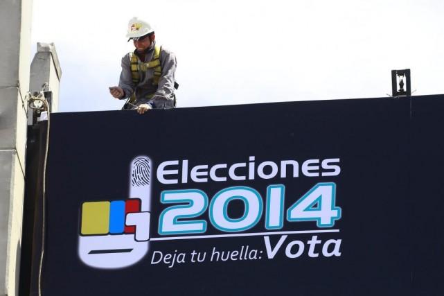 Un travailleur installe une bannière à l'entrée d'un... (PHOTO JOSE MIGUEL GOMEZ, REUTERS)