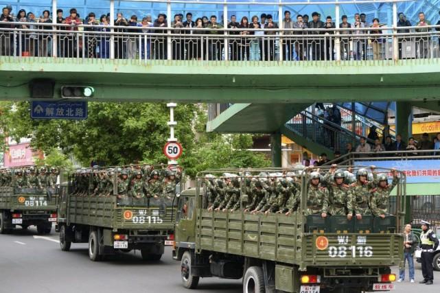 Des camions transportant des militaires arrivent àUrumqi, vendredi.... (PHOTO AP/KYODO NEWS)