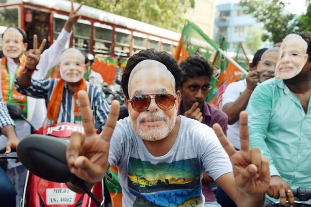 Des partisans du BJP arborent un masque à... (PHOTO PUNIT PARANJPE, AFP)
