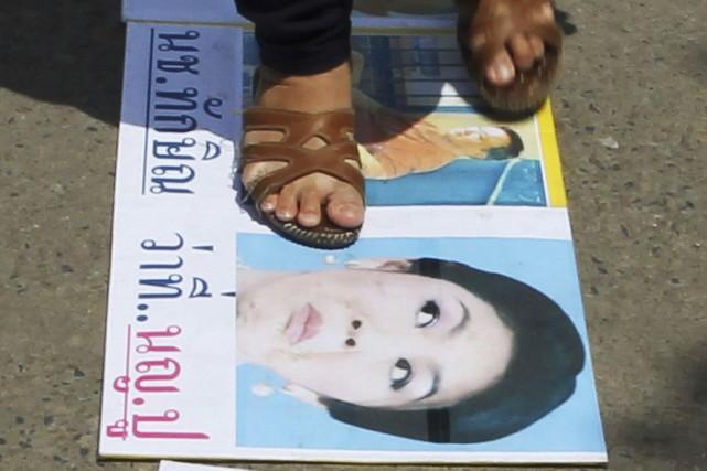Un militant anti-gouvernement piétine une pancarte à l'effigie... (PHOTO APICHART WEERAWONG, ARCHIVES AP)