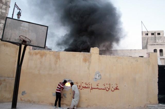 Deux hommes regardent par un trou dans un... (PHOTO ABDALRHMAN ISMAIL, ARCHIVES REUTERS)