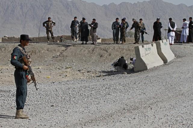Un policier afghan surveille le site où deux... (Photo Allauddin Khan, AP)