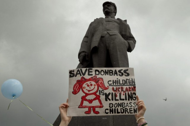 Une femme tient une pancarte demandant la protection... (PHOTO VADIM GHIRDA, AP)