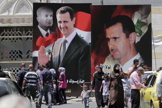 Des passants marchent devant des affiches géantes du... (PHOTO JOSEPH EID, AFP)