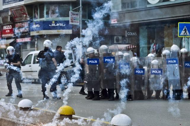 Des policiers se protègent des feux d'artifice lancés... (PHOTO OZAN KOSE, AFP)