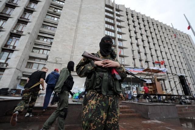 Un militant prorusse garde l'entrée d'un édifice du... (PHOTO VIKTOR DRACHEV, AFP)