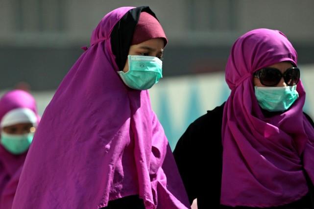 Plusieurs habitants du pays portent un masque chirurgical... (Photo Hasan Jamali, AP)