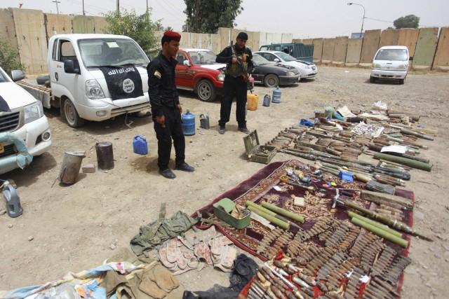 Les forces irakiennes exposent des armes confisquées vendredi... (Photo Reuters)
