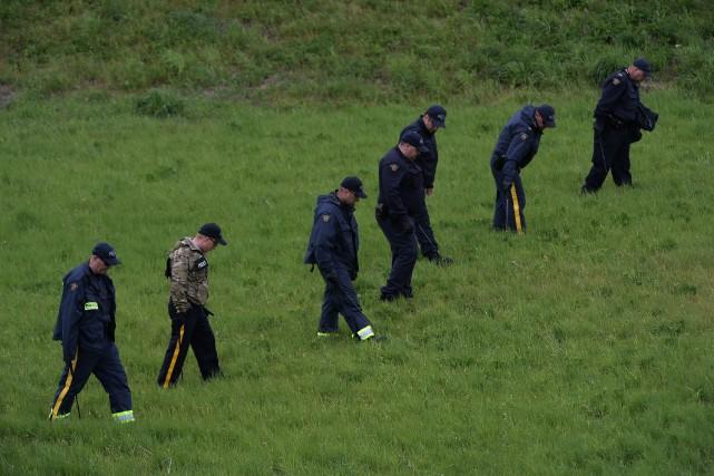 Quelques dizaines d'agents ont recherché des indices derrière... (Photo Sean Kilpatrick, La Presse Canadienne)