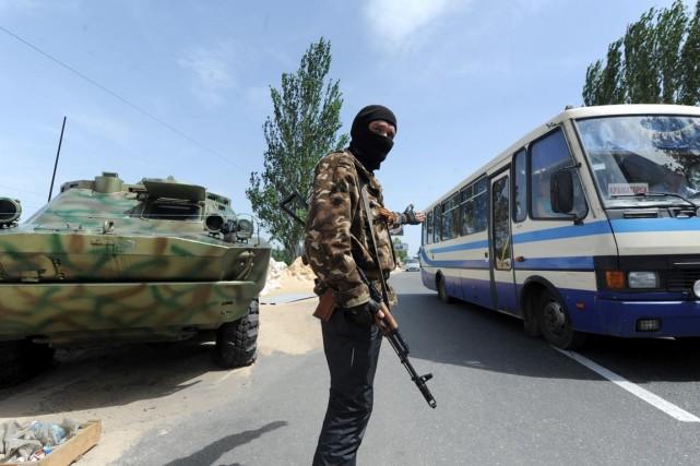 Un militant prorusse laisse passer un autobus à... (PHOTO VIKTOR DRACHEV, AFP)