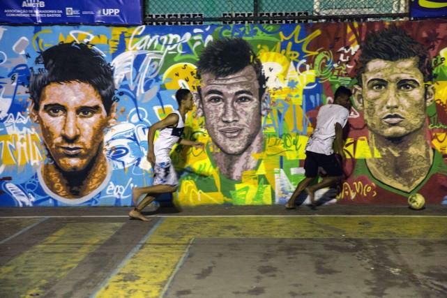 Des jeunes Brésiliens jouent au soccer devant une... (Photo Yasuyoshi Chiba, AFP)