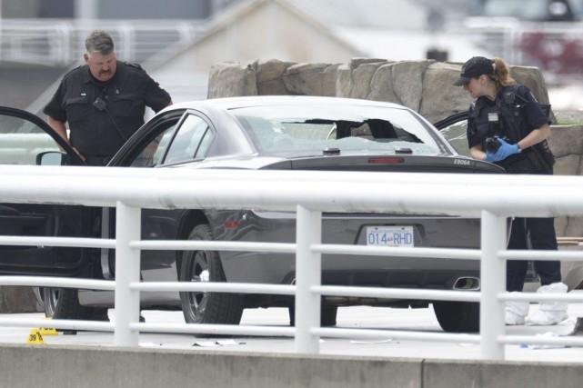 Des policiers examinent une voiture devant le centre... (Photo Jonathan Hayward, PC)